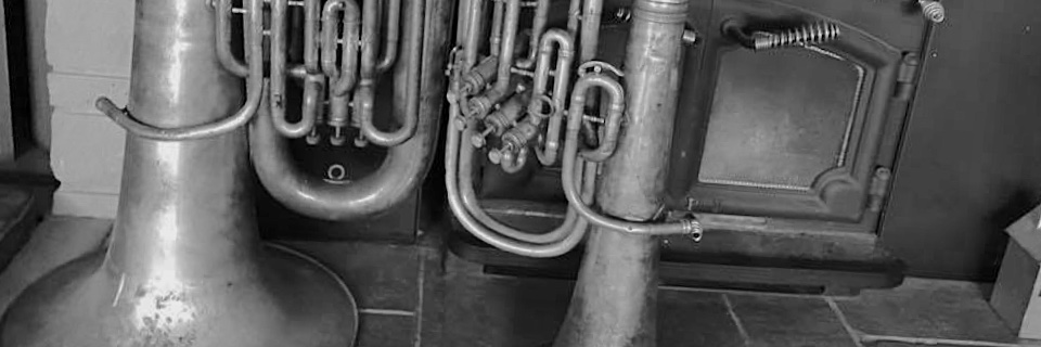 Image: E flat tuba and B flat euphonium in front of fireplace